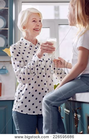 Drink It. Upbeat Elderly Woman In A Dotted Blouse Giving A Glass Of Milk To Her Little Daughter, Off