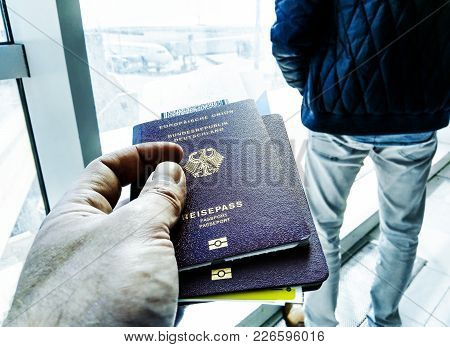 Male Hand Holding Passports And Boarding Pass At Airport Gate
