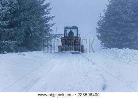 Red Snowblower Grader Clears Snow Covered Ski Resort Road In Mountains Or City Street. Winter Snowfl