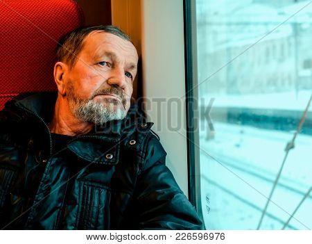 Bearded old man in train near window