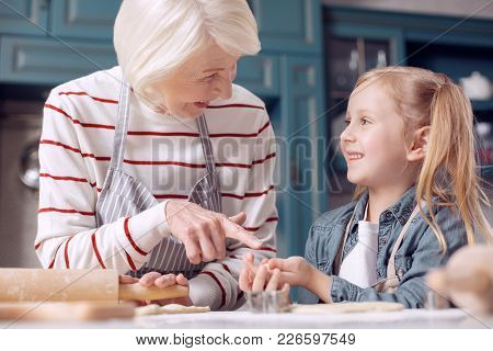 Content With Result. Cheerful Elderly Woman Pointing At A Little Cookie In The Hands Of Her Granddau