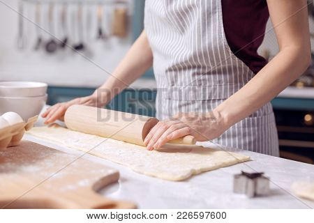 Deft Pastry Chef. The Close Up Of Delicate Hands Of A Young Female In An Apron Holding A Rolling Spi