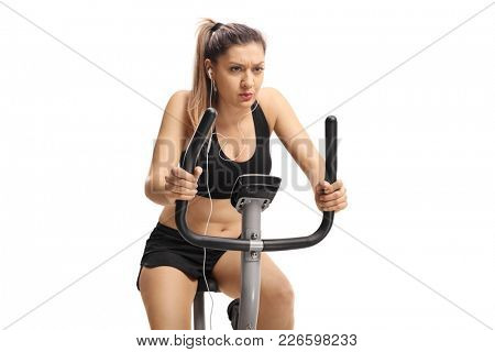 Woman exercising on a cross-trainer machine isolated on white background