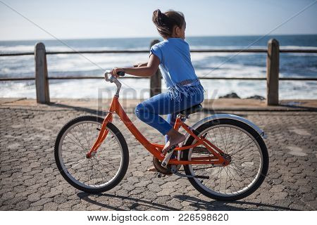Cape Town, Western Cape, South Africa, 11/01/2017. Girl Rides A Bike On The Seafront In Cape Town.