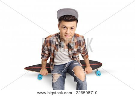 Teenage hipster sitting on a longboard and looking at the camera isolated on white background