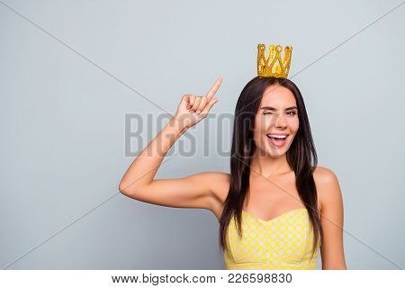 I'm queen of beauty! Where are my servants? Cheerful beautiful attractive pretty charming woman is pointing on the golden crown on her head and giving a wink, isolated on grey background, copy-space poster