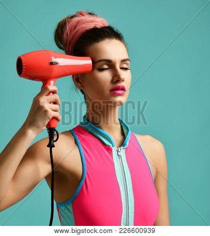 Happy Young Brunette Woman With Red Hair Dryer On Blue Mint Background. Hair Style Beauty Concept