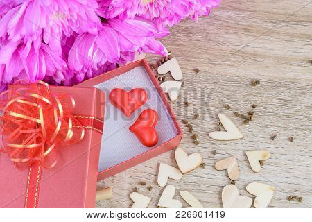 A Red Heart With Red Gift Box, Wooden Hearts Shape And Pink Flower On Wooden Table Background , Love