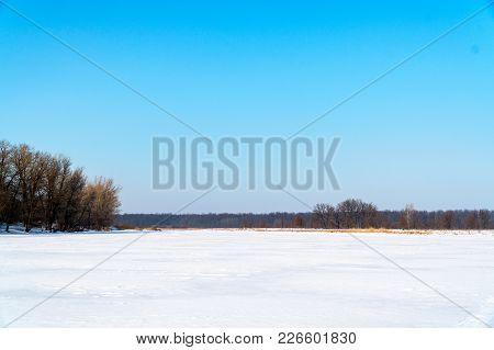 Winter Landscape. A Snow-covered Field, In The Distance Stands A Forest And A Blue Beautiful Sky