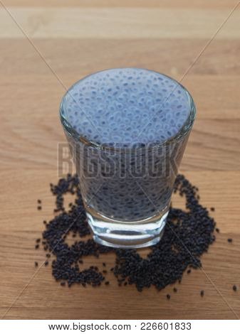 Swelled Sweet Basil Or Sabja Seeds In Shot Glass With Dried Seeds On Wooden Background Show Concept