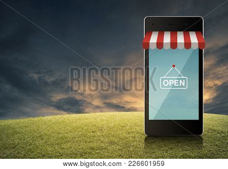 Modern Smart Mobile Phone With Online Shopping Store Graphic And Open Sign On Green Grass Field Over