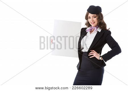 Beautiful Stewardess Holding Empty Board And Looking At Camera Isolated On White