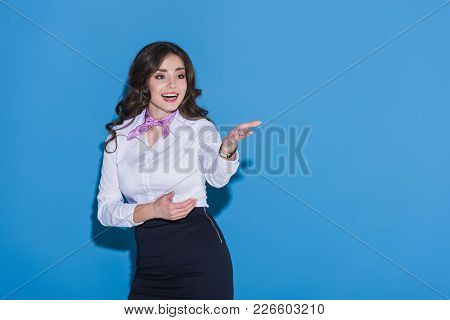 Attractive Stewardess Showing At Something On Blue