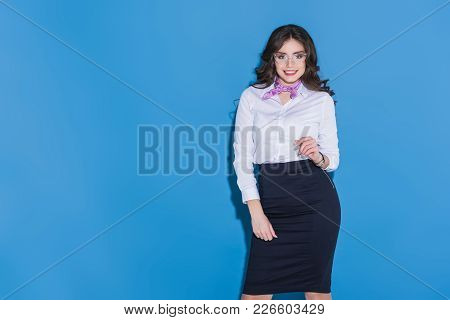 Attractive Smiling Stewardess Looking Away On Blue