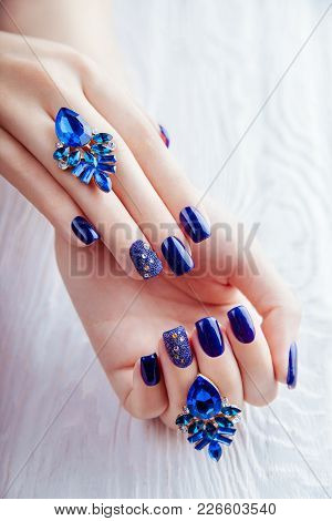 Blue Manicure With Earrings On White Wooden Background