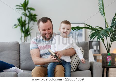 Photo of father and son reading book sitting on gray sofa