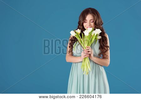 Beautiful Girl Sniffing Tulips Isolated On Blue
