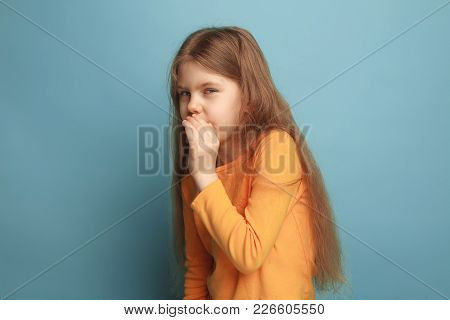 The Surprise, Delight. The Teen Girl On A Blue Studio Background Girl Whispers Someone A Secret. Fac