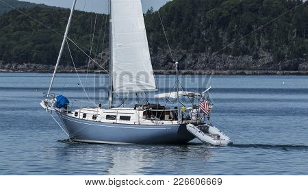 A Blue And White Sailboat Is Travelling In Frenchmans Bay Off Of The Coast Of Bar Harbor Maine On A