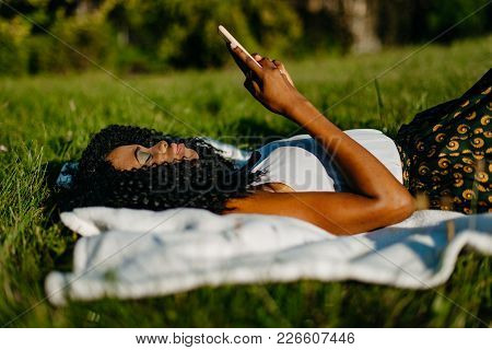 The Beautiful Young African Girl Is Laying On The Grass And Chatting, Texting And Browsing Via The M