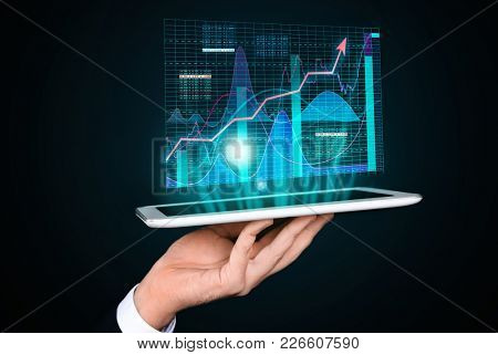 Broker holding tablet with projection of stock exchange data on dark background