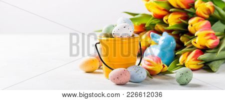 Easter Composition With Colored Quail Eggs Candies In Bucket And Spring Tulips Flowers. Holidays Con
