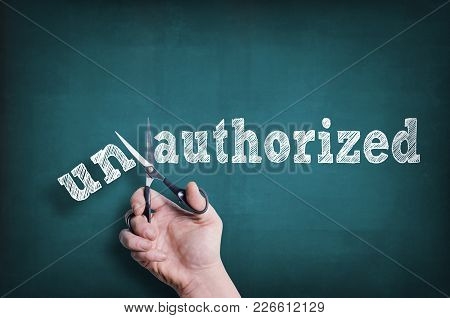 The Male Hand With Scissors Cuts Word Authorized From Unauthorized