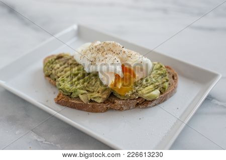 Poached Eggs And Avocado On Bread On A Plate