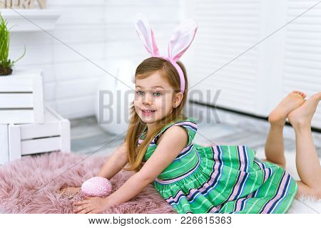 Close Up Of Four Years Old Girl With Bunny Ears And Big Egg In Her Hands On White Background Around