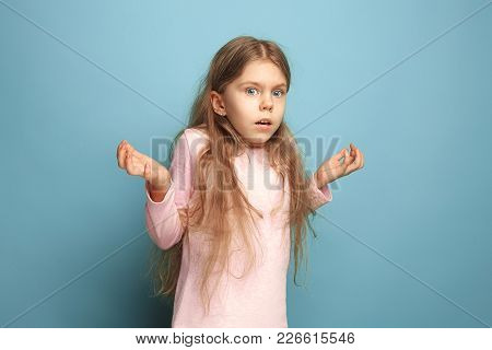 The Surprise, Bewilderment, Delight. The Surprised Teen Girl On A Blue Studio Background. Facial Exp