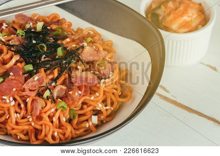 Korean Hot And Spicy Instant Noodle In Black And White Bowl Topped With Bacon, Sesame, Seaweed And C