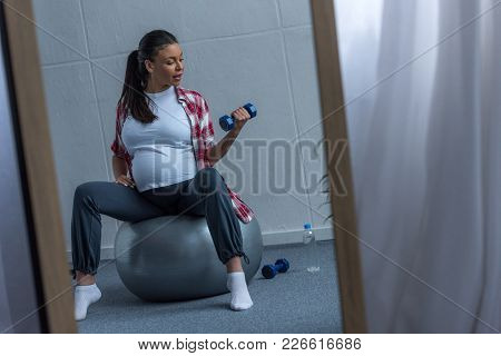 Mirror With Reflection Of African American Pregnant Woman Sitting On Fit Ball And Training With Dumb