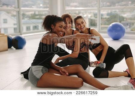 Smiling Young Girls Taking Selfie In Gym