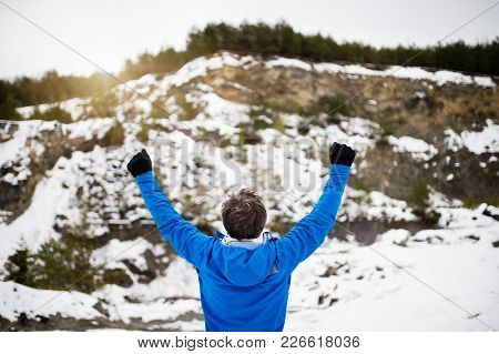 Senior Man Jogging Outside In Winter Nature, Hands Up. Rear View.