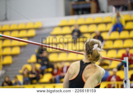Unrecognizable Sportswoman Performing High Jump Over Bar On Track And Field Competition
