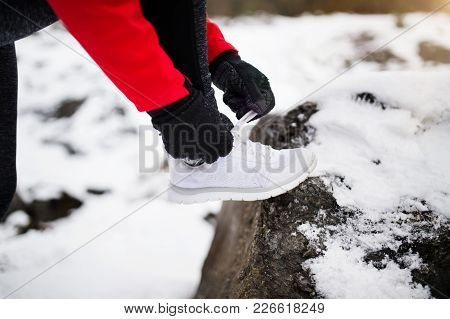 Unrecognizable Woman Jogging Outside In Winter Nature, Tying Shoelaces. Close Up.