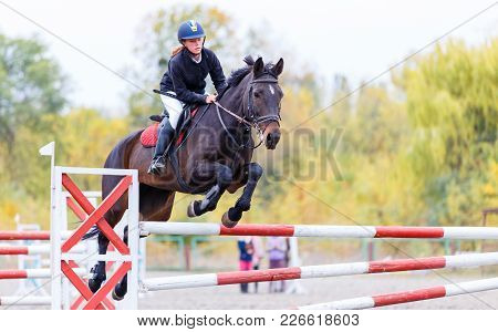 Young Rider Girl On Bay Horse Jumping Over Barrier On Equestrian Sport Competition. Horseback Girl O
