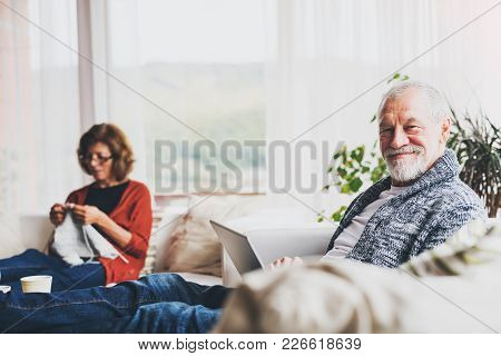 Happy Senior Couple Relaxing At Home. A Woman Knitting And A Man Using A Laptop.