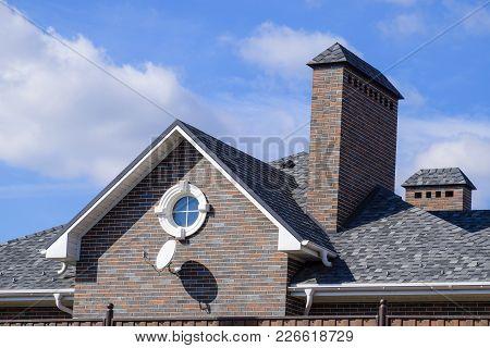 Asphalt Shingle. Decorative Bitumen Shingles On The Roof Of A Brick House