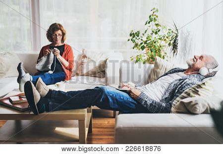 Happy Senior Couple Relaxing At Home. A Woman Knitting And A Man With Tablet Listening To Music.