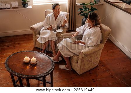 Two Women Talking While Waiting For Spa. Female Friends In Bathrobe Sitting On Chair Having Herbal T