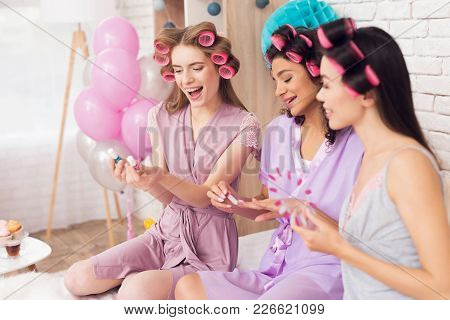 Three Girls With Curlers In Their Hair Doing Nail Polish. They Are Celebrating Women's Day March 8.