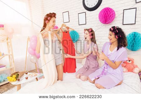 Three Girls With Curlers In Their Hair Coosing Between Two Dresses. They Are Celebrating Women's Day
