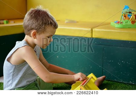 Handsome Pre-school Boy In T-shirt Enthusiastically Plays Toys In Playroom