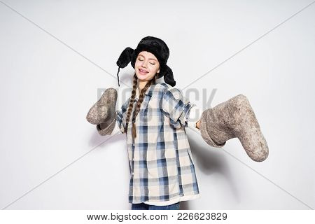 Funny Happy Russian Girl In A Cap With Ear-flaps Holds Gray Felt Boots