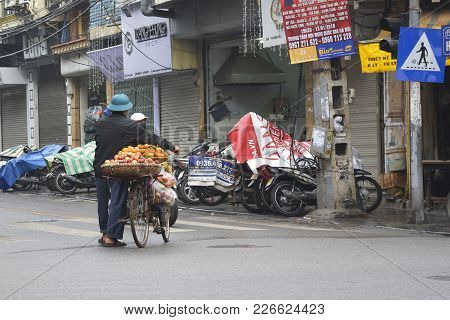 Hanoi, Vietnam - December 13th 2017. A Street Seller Sells Apples And Oranges From His Bike In The H