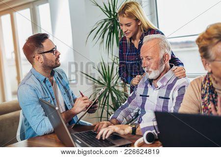 Young Volunteers Help Senior People On The Computer. Young People Giving Senior People Introduction