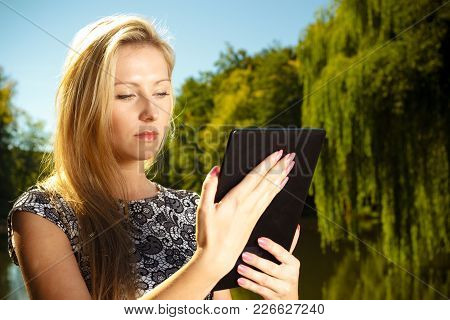 Technology, Outdoor Relaxation Concept. Woman In Park, Relaxing And Using Tablet, Ebook Spending Her