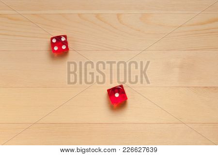 Red Dice On A Light Brown Wooden Background