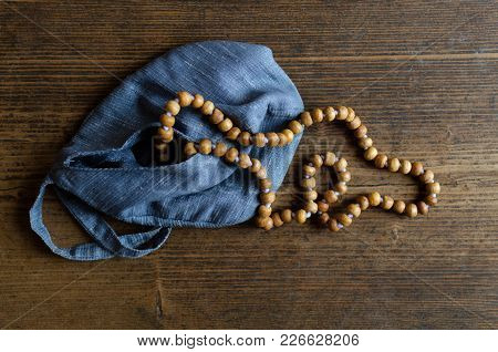 Wooden Rosary. Wooden Rosary In Blue Bag On A Wooden Floor